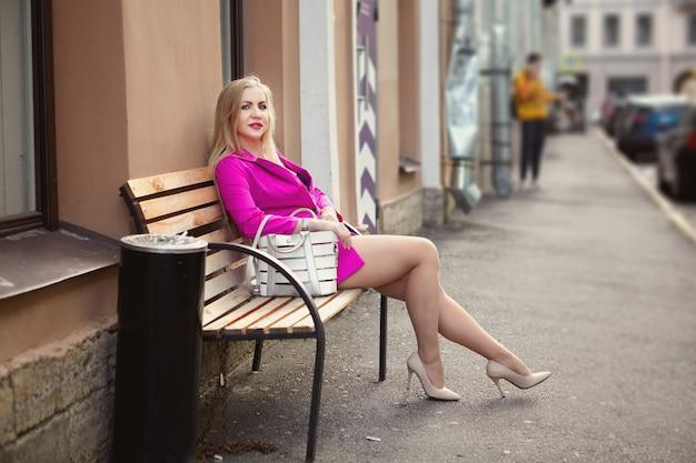 Mulher russa de meia-idade, vestida com roupas cor de rosa e salto agulha, senta-se no banco de uma área para fumantes na rua de uma cidade europeia.