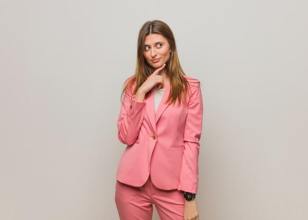 Mulher russa de negócios jovem duvidando e confusa