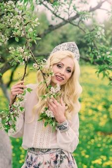 Mulher russa elegante com vestido tradicional folclórico nacional e cocar kokoshnik eslavo no jardim