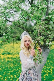 Mulher russa elegante em vestido folclórico nacional tradicional, cocar eslavo, flores brancas de primavera.