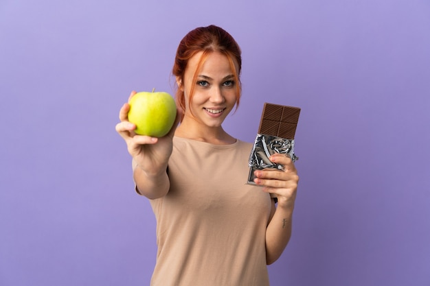 Mulher russa isolada em roxo pegando um comprimido de chocolate em uma das mãos e uma maçã na outra
