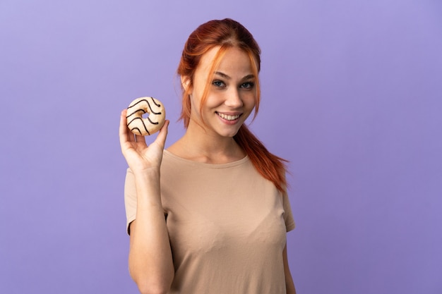 Mulher russa isolada no roxo segurando uma rosquinha e feliz