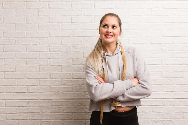 Mulher russa jovem fitness, segurando uma fita métrica