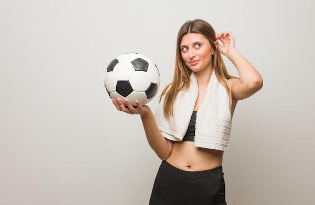 Mulher russa jovem fitness sonhando em alcançar objetivos e finalidades. segurando uma bola de futebol.