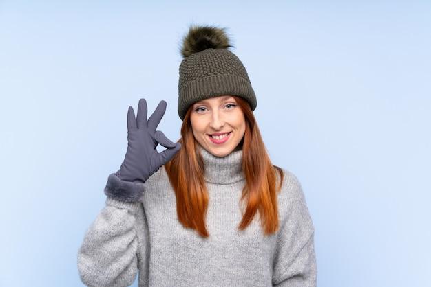 Mulher russa jovem ruiva com chapéu de inverno sobre azul isolado, mostrando um sinal de ok com os dedos