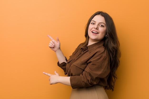 Mulher russian curvy nova excitada apontando com os dedos indicadores afastado.