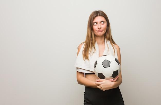Mulher russian da aptidão nova cansada e furada. segurando uma bola de futebol.