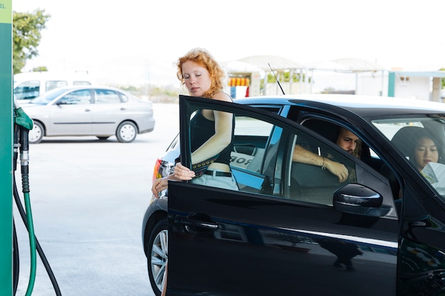 Mulher, saindo, de, car, em, posto gasolina