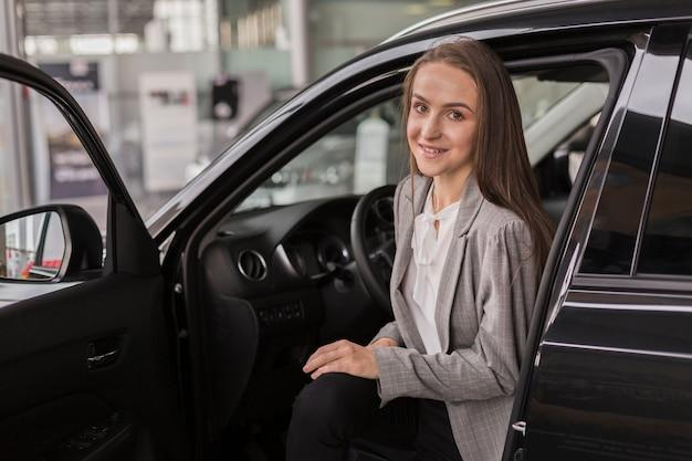 Mulher saindo de um carro moderno