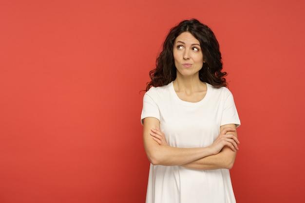 Mulher sarcástica e duvidosa olhar crítico com rosto cético de lado para espaço de cópia vazio sobre a parede vermelha