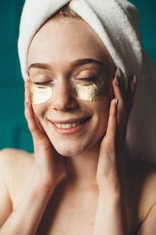 Mulher sardenta com cabelo ruivo aplicando tapa-olho dourado sorrindo para a câmera após o banho