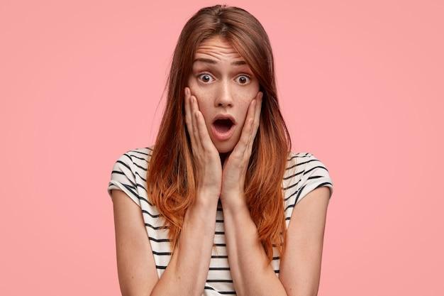 Mulher sardenta com o queixo caído ao perceber algo surpreendente, usa uma camiseta listrada casual contra uma parede rosa