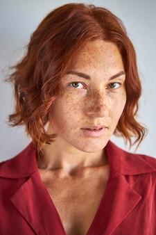 Mulher sardenta de cabelo ruivo olhando para a câmera, jovem de beleza natural, com olhar penetrante
