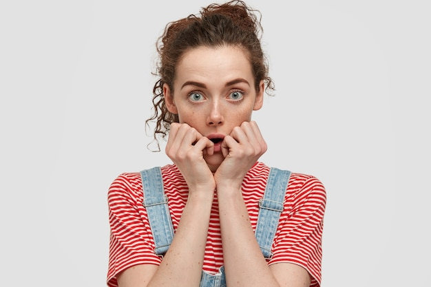 Mulher sardenta de olhos verdes mantém as mãos perto da boca, parece perplexa, tem cabelo escuro e encaracolado, usa camiseta listrada casual com macacão jeans, isolada sobre parede branca. pessoas e maravilha