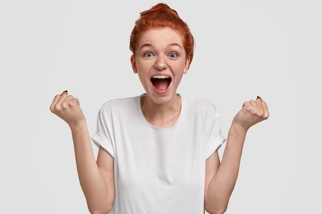 Mulher sardenta, emotiva e cheia de alegria, com cabelos ruivos, levanta os punhos e exclama em voz alta, anima a amiga, grita palavras de apoio, usa uma maquete casual de camiseta branca, modelos e gestos
