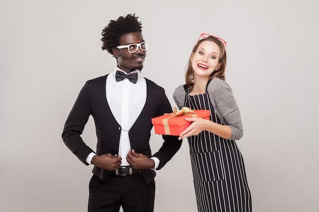 Mulher sardenta segurando uma caixa de presente, homem africano em pé perto e sorrindo, foi ele quem lhe deu um presente. foto do estúdio, fundo cinza