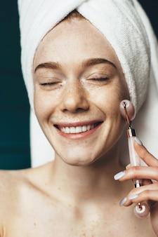 Mulher sardenta usando um rolo de massagem facial sorrindo enquanto cobre a cabeça com uma toalha e posa com os ombros nus
