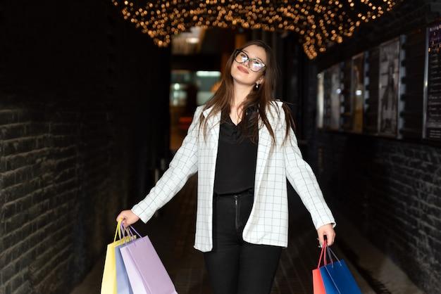 Mulher satisfeita caminha pela cidade à noite depois de fazer compras bem-sucedidas com as compras em suas mãos.