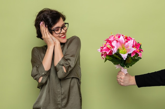 Mulher satisfeita com cabelo curto parecendo surpresa e feliz sorrindo alegremente enquanto recebe buquê de flores de seu namorado comemorando o dia internacional da mulher, 8 de março