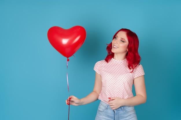Mulher satisfeita com cabelo ruivo olhando para um balão voador vermelho em forma de coração