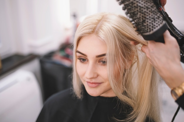 Mulher satisfeita com estilo de cabelo no salão de beleza Foto Premium