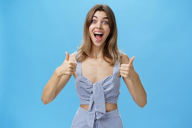 Mulher satisfeita com o resultado perfeito sorrindo animada com um sorriso feliz mostrando gesto de polegar para cima, posando em combinação elegante fechada sobre a parede azul, olhando emocionada e encantada