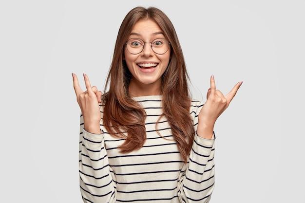 Mulher satisfeita com o sorriso dentuço, levanta as duas mãos e mostra o cartaz do rock n roll, vestida com um macacão listrado, modelos encostados na parede branca, ouve música pesada, gosta de rock. hipster gosta de música