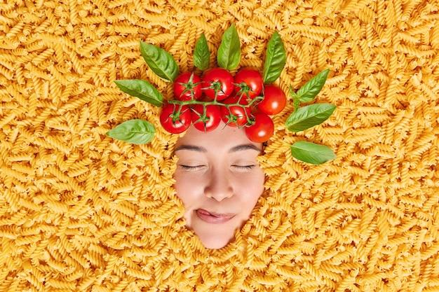 Mulher satisfeita com os olhos fechados lambe os lábios de satisfação, sonha com uma refeição saborosa de macarrão cercada por macarrão cru, tomate vermelho e folhas de manjericão acima da cabeça