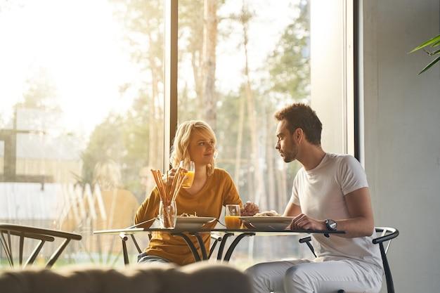 Mulher satisfeita com um copo de suco de laranja sorrindo para o marido na mesa
