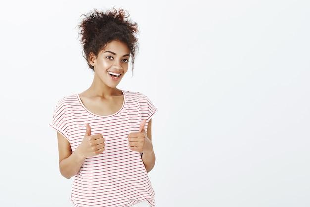 Mulher satisfeita com um penteado afro posando no estúdio