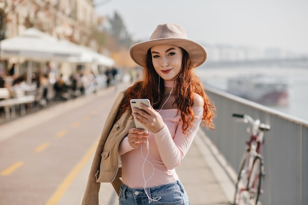 Mulher satisfeita com um sorriso malicioso segurando um telefone perto do rio da rua