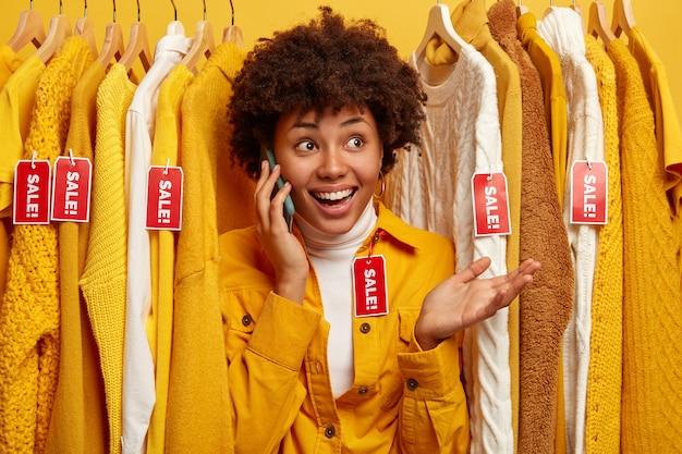 Mulher satisfeita conversa ao telefone com amiga, pede conselhos sobre o que melhor comprar, escolhe roupa na loja de roupas, gosta de fazer compras, fica com a palma da mão levantada. conceito de venda de compras de varejo.