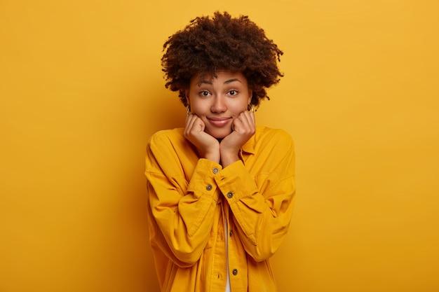 Mulher satisfeita de cabelos cacheados com penteado afro, mantém as mãos sob o queixo, parece com expressão facial sensual