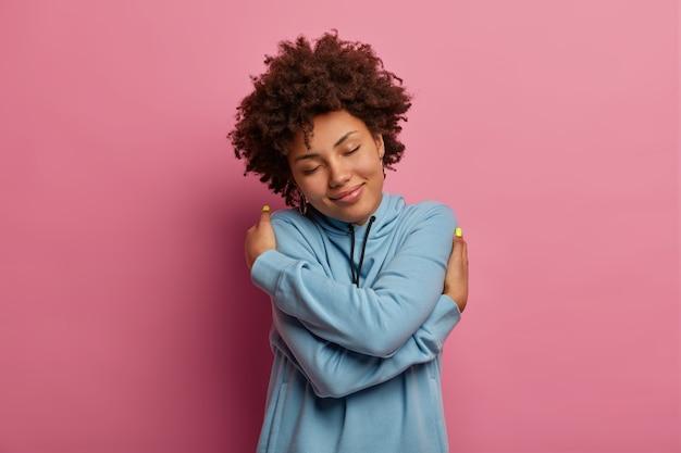 Mulher satisfeita de pele escura com cabelo afro, se abraça