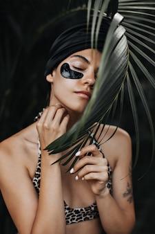 Mulher satisfeita em turbante posando com os olhos fechados. mulher jovem incrível fazendo tratamento de pele no fundo da natureza.