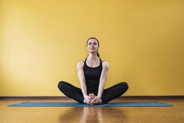 Mulher satisfeita praticando ioga fazendo exercício budista konasana em pose de borboleta se exercitando sentada em uma esteira contra uma parede amarela