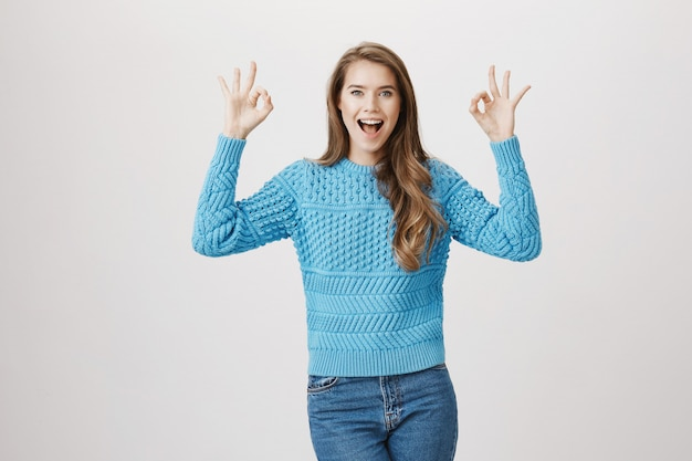 Mulher satisfeita, regozijando-se, mostre o gesto de aprovação aprovado
