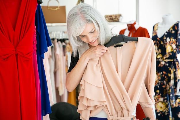 Mulher satisfeita segurando e olhando por cima do vestido de festa com cabide perto da prateleira com roupas em loja de moda. mulher às compras na boutique. conceito de consumismo