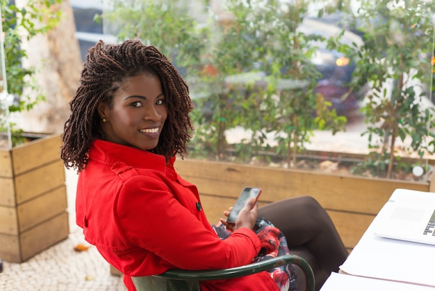 Mulher satisfeita segurando smartphone e sorrindo