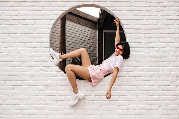 Mulher satisfeita, sentada na parede de tijolos e olhando para a câmera. foto ao ar livre do alegre modelo feminino em óculos de sol rosa e shorts.