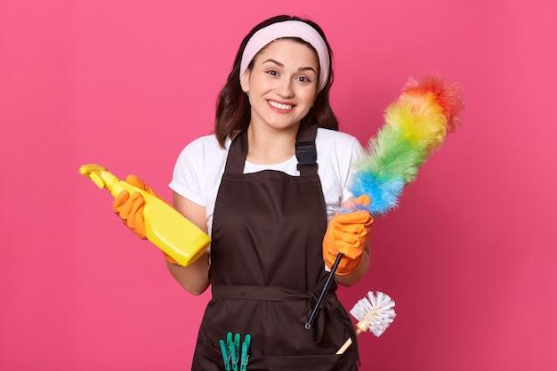 Mulher satisfeita vestida com camiseta casual, avental e faixa de cabelo, segurando detergente e espanador