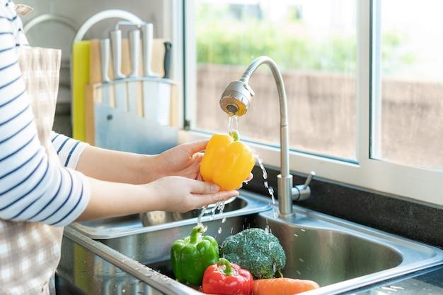 Mulher saudável asiática lavando pimentão amarelo e outros vegetais acima da pia da cozinha