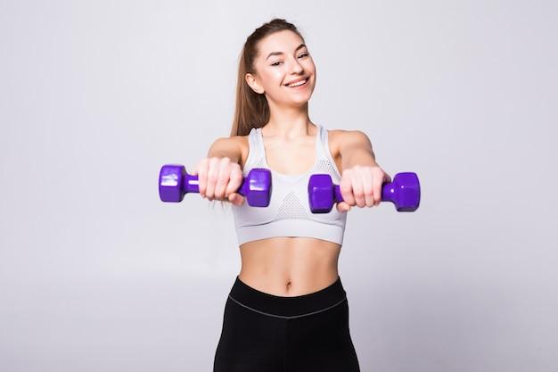 Mulher saudável com halteres malhando isolados na parede branca. conceito de ginásio de fitness