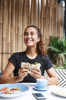 Mulher saudável com o bronzeado, sentado com uma camiseta no terraço do café, tomando café da manhã e bebendo café.