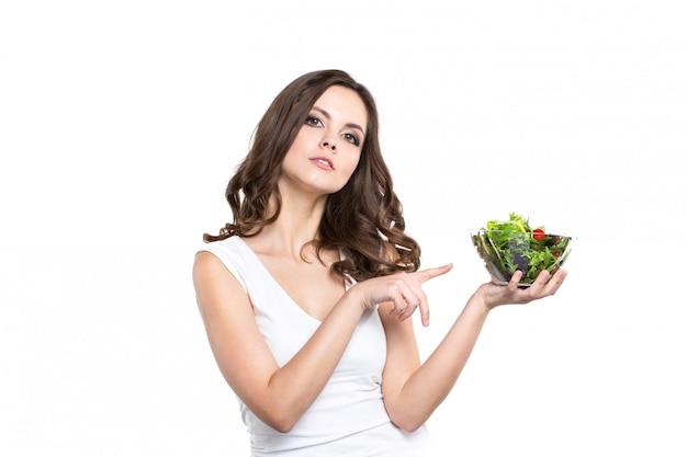 Mulher saudável com salada no fundo branco.