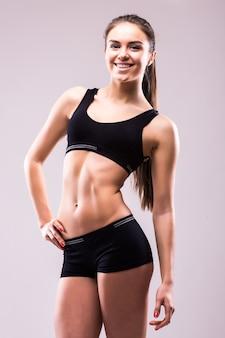 Mulher saudável, confiante e satisfeita em roupas esportivas com as mãos nos quadris