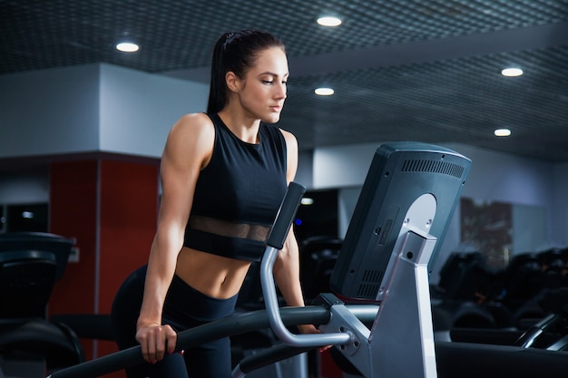 Mulher saudável e desportiva apta a fazer exercícios cardiovasculares na passadeira. atleta feminina exercitando-se no stepper no moderm gym