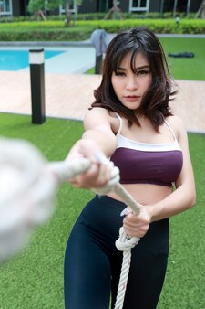 Mulher saudável e desportiva nova que faz o exercício com uma corda ao ar livre