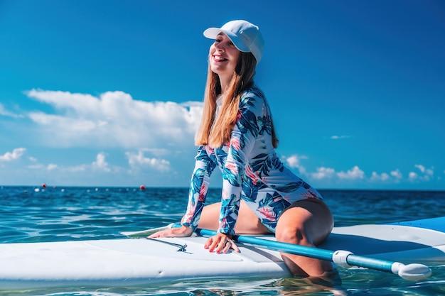 Mulher saudável e feliz em biquíni relaxando em uma prancha de surfe flutuando no mar azul-turquesa