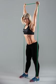 Mulher saudável esportes com os braços erguidos, estendendo-se com borracha elástica